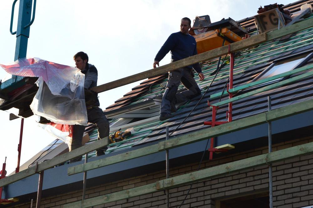 De dakwerkers in volle actie. De dakpannen liggen er op.